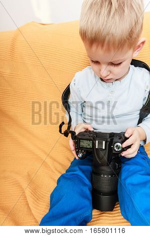 Technology and childhood. Discovering and fun. Child play and take photo in home. Boy wear white shirt and blue trousers hold camera.