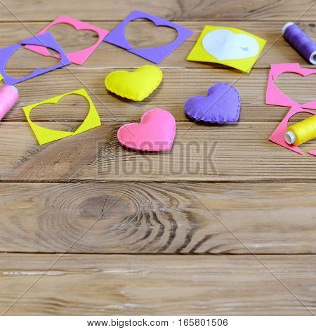 Hand sewing hearts diy. Handmade hearts diy for Valentine's day, mother's day or wedding. Sewing supplies on a wooden table. Easy and cheap crafts from felt. Closeup