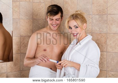 Smiling Young Couple Finding Out Results Of A Pregnancy Test In Bathroom