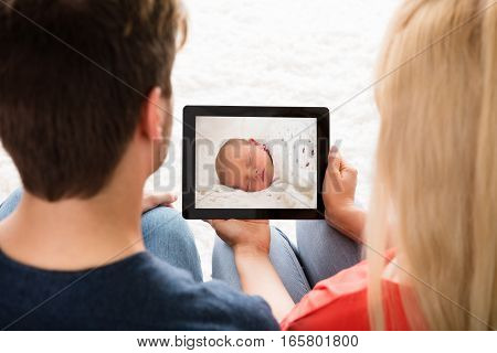 Close-up Of Young Couple Sitting Looking At Baby's Photo On Digital Tablet At Home