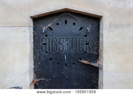 Dark blue closed steel door in a stone wall of an old crypt. The weathered iron entry of the tomb has a triangular arch and is decorated with carvings and holes.