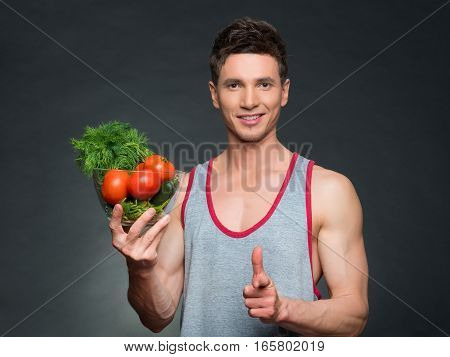 Young fittness trainer and nutritionist holding a bowl of vegetables, on black background
