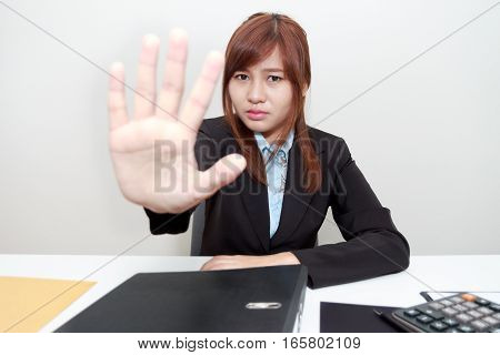 Portrait of Business woman says no or hold on at her office.