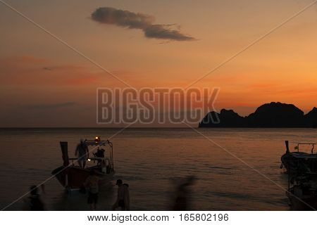A silhouette of boat, rocks and people against sunset