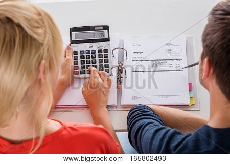 Close-up Of Couple Calculating Invoices Tax And Retirement Money Using Calculator On Desk At Home