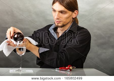 Alcohol liquor drinking tasting relax concept. Wine steward fills glass. Young male waiter pours drink into cup.