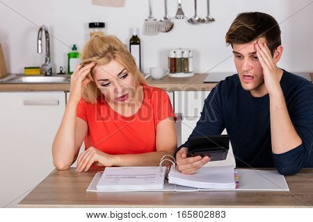Worried Young Couple Calculating Their Bills To Save Tax And Insurance Money At Home
