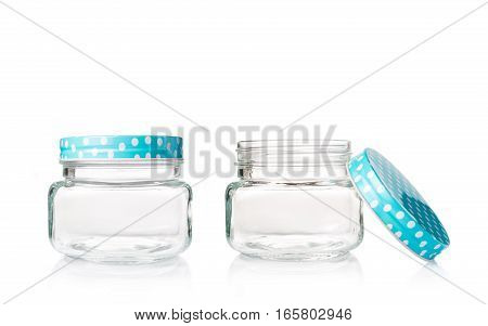 two empty glass jars with one open and one close blue dotted lids on white background copyspace on top