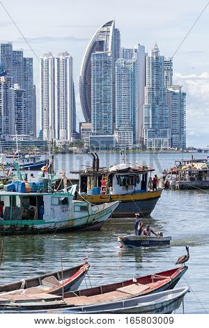 June 15, 2016 Panama City, Panama: small fishing boats floating on the water by the fish market with the modern downtown highrise buildings in the background the fish market with the modern downtown highrise buildings in the background
