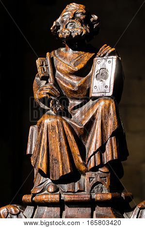 A carved wooden religious figure holding a book