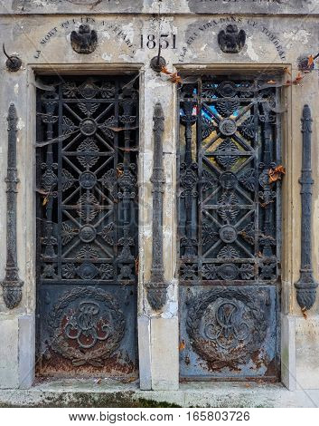 Two seperate ornate steel doors, rusting and decaying. Each iron door is an entry to a seperate abandoned tomb / crypt at a graveyard. Both are decorated with flowers, faces, eagles, and Latin inscriptions.