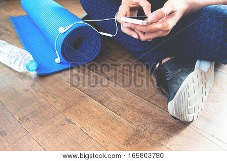 Female fitness using mobile phone with copy space
