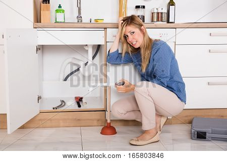 Young Frustrated Woman Having Sink Problem Trying To Fix Sewer Drainage In Kitchen