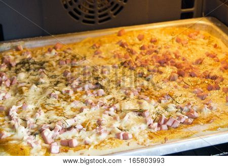 pizza in the oven the pie with sausage and cheese in the oven