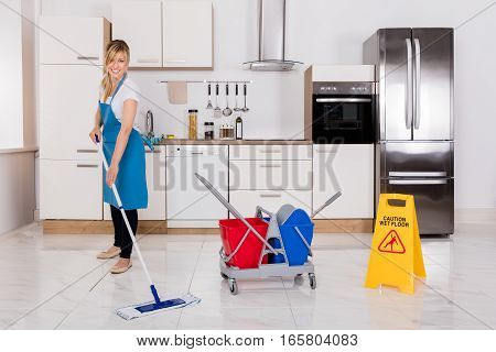 Cleaning Service Maid Using Mop To Clean Kitchen Floor