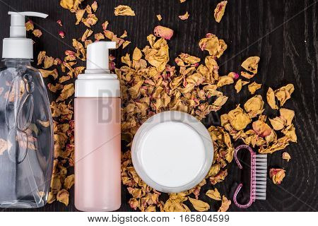 Petals, dry flowers and women's accessories on black background. Flat lay, Top view. Copy space