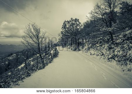 Black & white image of snow covered mountain road in the Balagne region of Corsica with a single set of footsteps and view of the valley and Mediterranean sea beyond