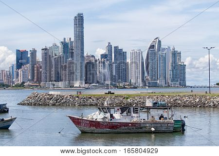 June 15, 2016 Panama City, Panama: small fishing boats floating on the water with the modern downtown highrise buildings in the background