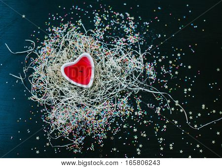 Candle in the shape of a heart in the straw and confetti