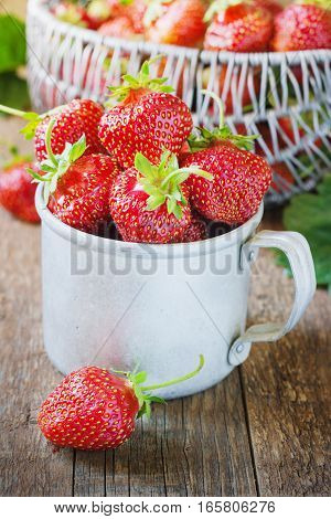 Red berry strawberry in metal mug on old rustic wooden background. Background from freshly harvested strawberries. Strawberry background.