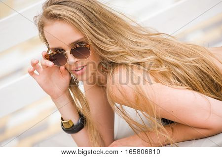 beautiful woman resting by the pool.blonde sunbathing on the loungers by the pool