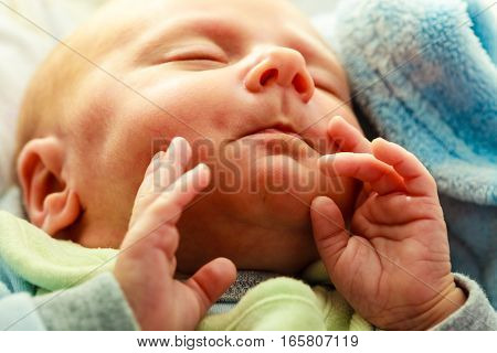 Little newborn baby in pyjamas lying on back with hands close to mouth and sleeping in bedding. Family parenthood childhood concept.