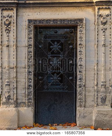 Closed dark black iron door in a stone wall. The entry to this old tomb is ornate with geometric and floral decorations. The rectangular doorframe contains ornaments chiseled into the stone. The crypt is abandoned and antique, located at an old cemetery.