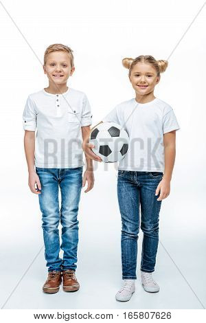 Two smiling children standing with soccer ball and looking at camera on white