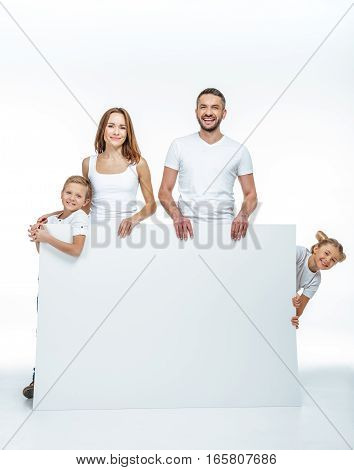 Happy family in white t-shirts holding blank card and looking at camera isolated on white