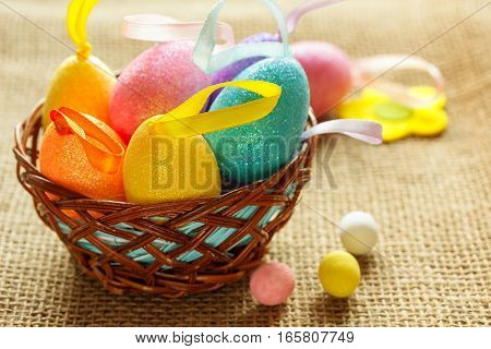 Easter still life in a country style with colored eggs. Easter eggs in the decorative nest. Soft focus.