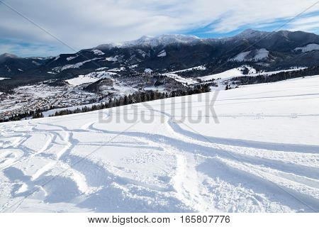 Ski with ski tracks - beautiful winter day - view from the mountain top to the valley