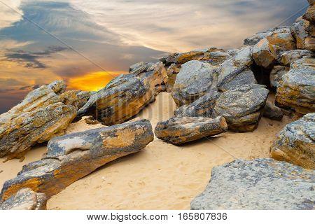 Stone desert. Old rocks on yellow sand on fantastic sunset background .