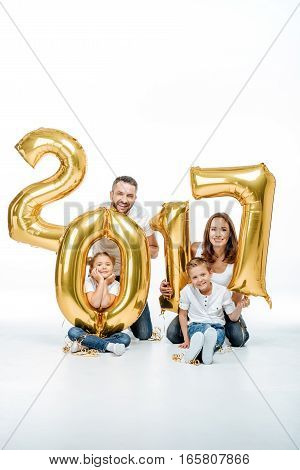 Happy family holding golden balloons on white background