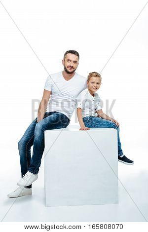 Smiling father with cute little son sitting together and looking at camera isolated on white