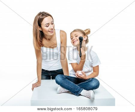 Smiling mother looking at adorable little daughter with makeup brush and face powder isolated on white