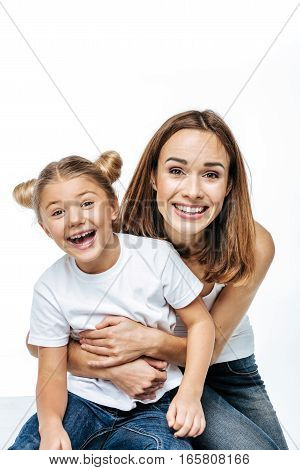 Smiling mother and daughter having fun together and looking at camera isolated on white