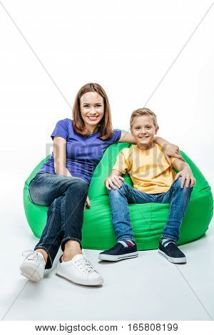 Smiling mother with son sitting together in sack-chair and looking at camera isolated on white