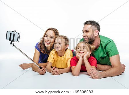 Happy family in colorful t-shirts taking selfie isolated on white