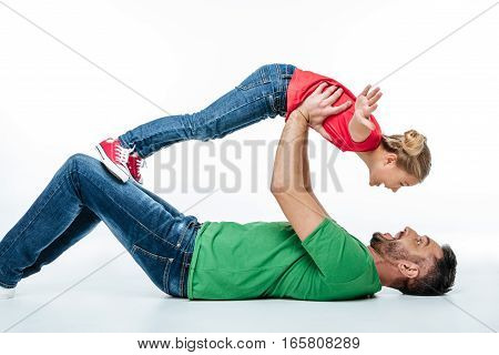 Happy father and daughter having fun together while lying on floor