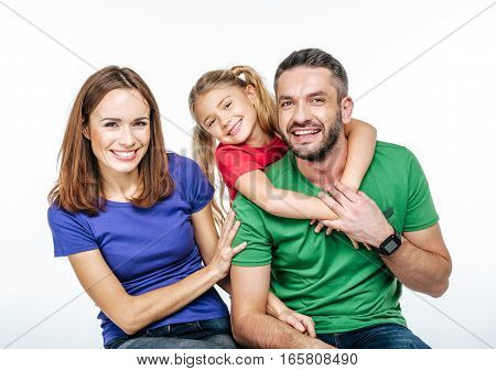 Young family in colorful t-shirts hugging and looking at camera