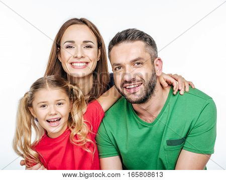 Portrait of Parents with little daughter smiling and looking at camera isolated on white