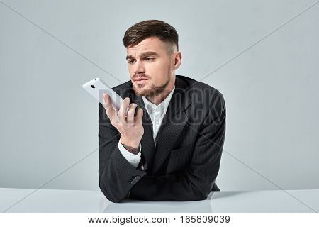 Handsome young man talking on the mobile phone while sitting at his working place in office. Emotions