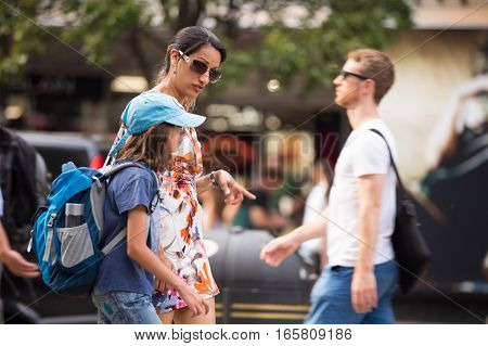 London, UK - August 24, 2016: Mother and son walking in Oxford street, main destination for shipping in London