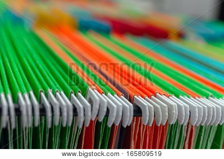 Abstract background of colorful hanging file folders in drawer. Stock photo