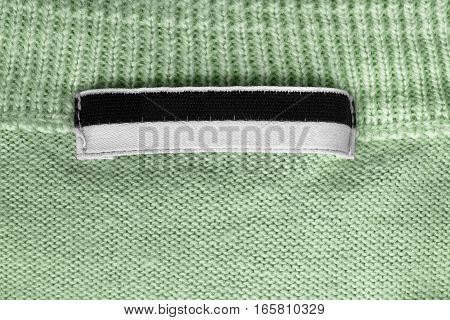 Black and white clothes label on green knitted background