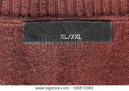Size clothes label on brown knitted cloth