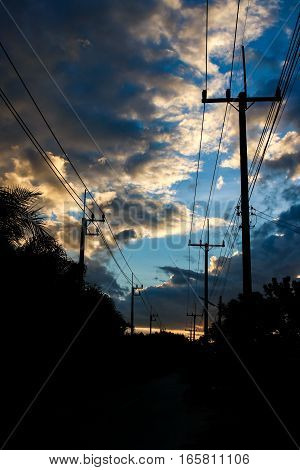 Silhouette power electric pole in evening time , sunset sky and  electrical pole structure, sunrise.