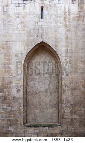 An empty doorframe in a stone wall. The arch of the frame is pointed as in gothic style. It reminds of a blocked passage or gateway, an insuperable obstacle in the way not letting anyone pass through.