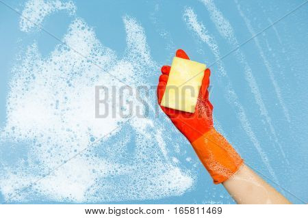 hand dressed rubber glove cleaning glass window pane with sponge and detergent , close-up. Cleaning concept on blue background