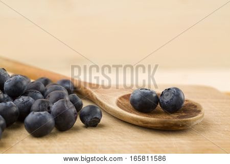 Blueberry on wooden spon ower wooden table
